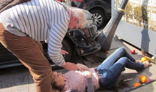 Мужчина оказывает первую помощь женщине в шоковом состоянии после ДТП